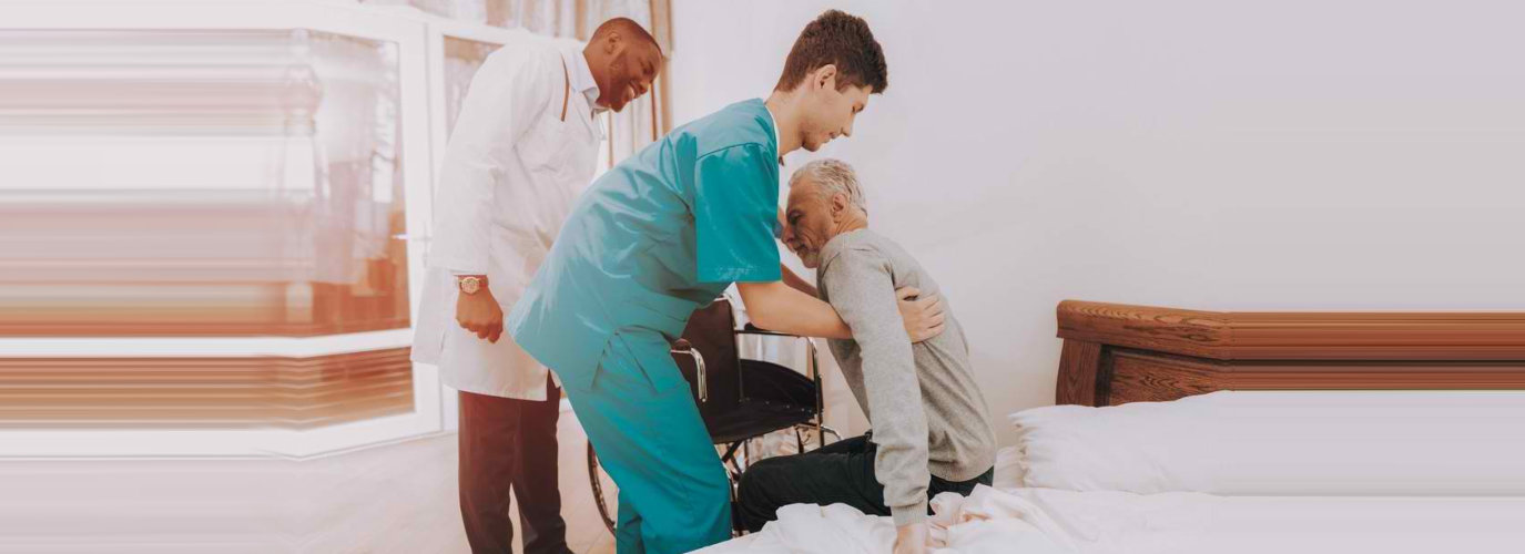 medical staff with a doctor helping a senior man to get up